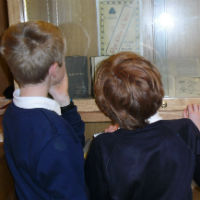 Students looking at Balliol Boys Club memorablia from WW1