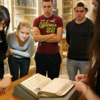 Publishing students from Oxford Brookes look at a medieval manuscript